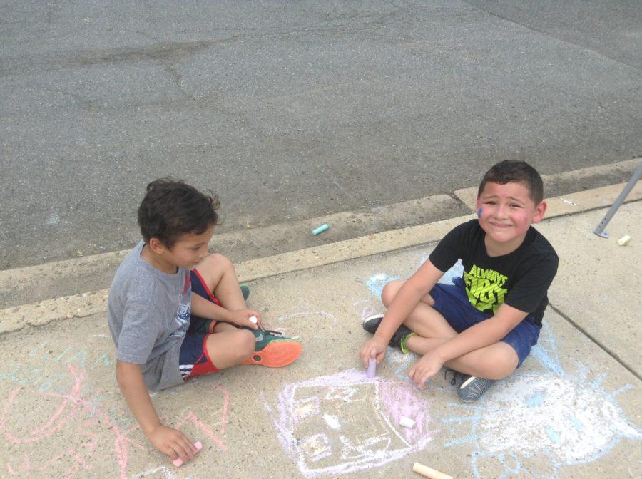 children coloring sidewalk with chalk